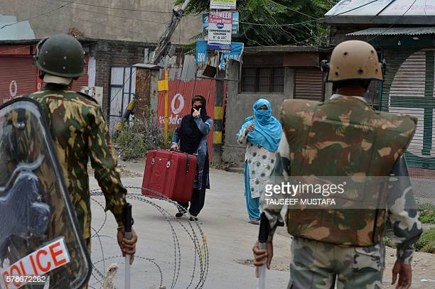 Indian paramilitary troopers stand guard as Kashmiri women approach them on the 14th day of a curfew in downtown Srinagar on July 22 2016 Residents...