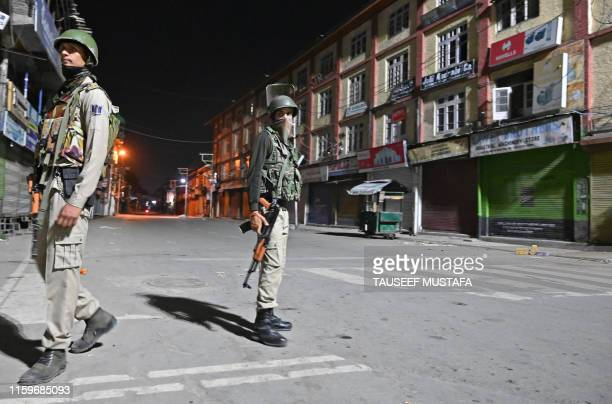 Indian paramilitary troopers stand guard at a roadblock at Maisuma locality in Srinagar on August 4 2019 Fears of an impending curfew in the disputed...