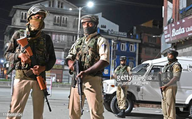 Indian paramilitary troopers stand guard at a roadblock at Maisuma locality in Srinagar on August 4, 2019. - Fears of an impending curfew in the...