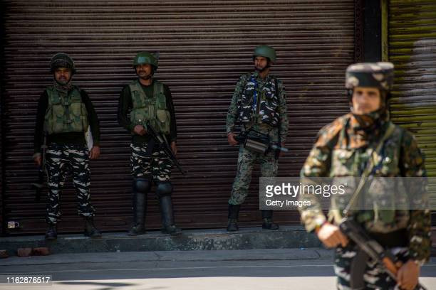 Indian paramilitary troopers stand guard in front the shuttered shops in the deserted city center on August 20 2019 in Srinagar the summer capital of...