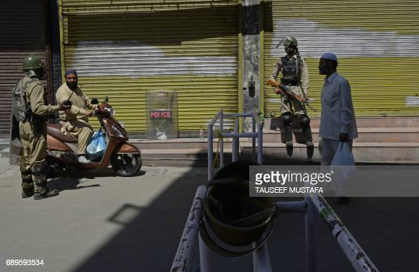 Indian paramilitary troopers stop a Kashmiri Muslim man during a curfew in central Srinagar on May 29, 2017. Authorities imposed a curfew in many...