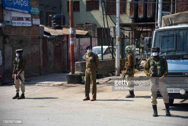 Indian paramilitary troopers wearing protective masks stand on guard during the restrictions imposed as a precautionary measure against the spread of...