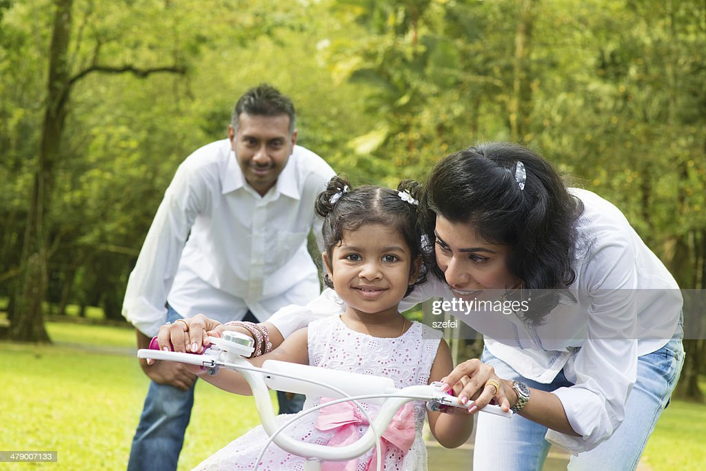 Indian  parent teaching child to ride a bike : Stock Photo