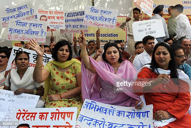 Indian parents wave placards and shout slogans during a protest in New Delhi on April 10 against recent increases in school fees and related items...