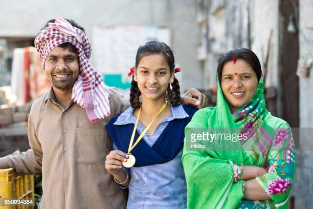 indian parents with daughter holding medal - teen awards stock photos and pictures