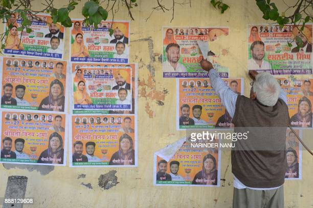 Indian Parsotam Lal removes election campaign posters on a wall outside his house in Amritsar on December 8 2017 / AFP PHOTO / NARINDER NANU