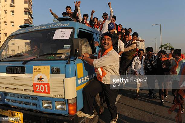 Indian participants board a media vehicle as they gesture and chant during the 'Run For Unity' to mark the 63rd death anniversary of Sardar...