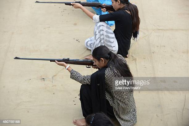 Indian participants fire 22 bore rifles during a fiveday firearms training programme for women aged 15 and above at the Ahmedabad City Police firing...