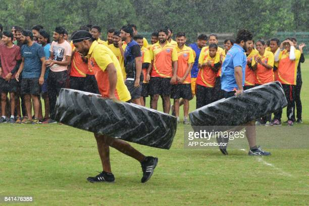 Indian participants take a part in a race carrying tyres following celebrations of National Sports day at Guru Nanak Dev University in Amritsar on...
