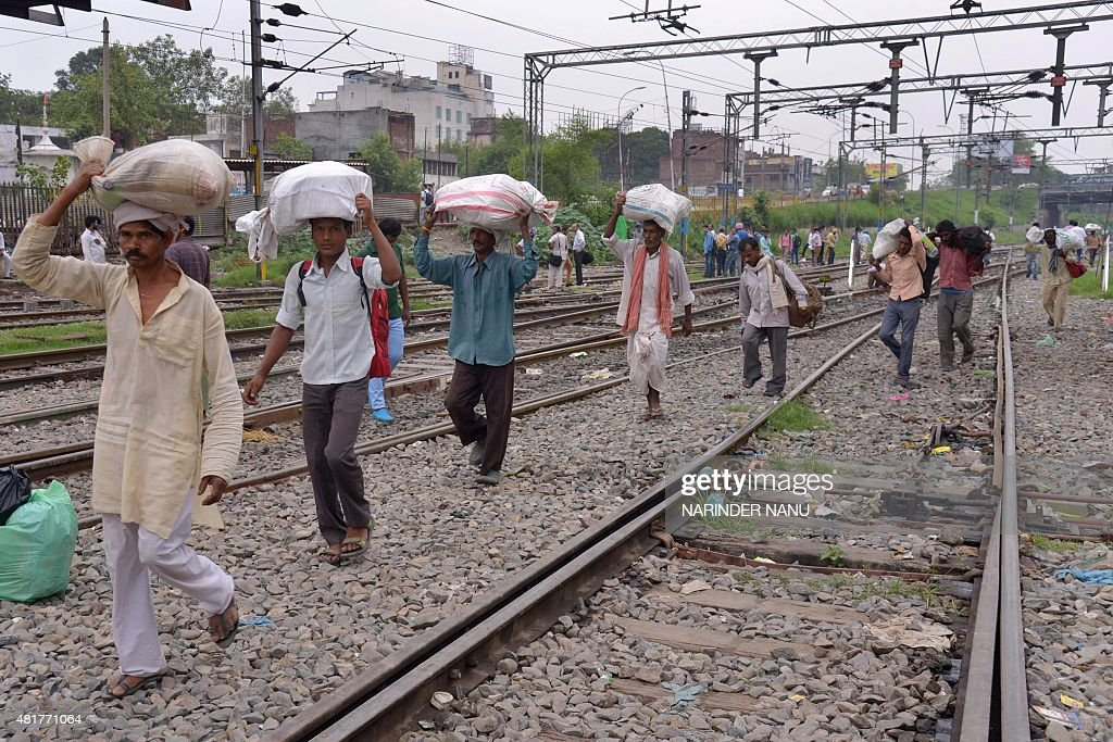 Indian passengers carry their baggage as they walk towards the railway station in Amritsar on July 24 2015 Passengers are facing inconvenience as...