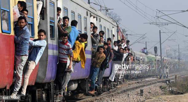 Indian passengers hang onto a train as it departs from a station on the outskirts of New Delhi on February 28 2017 India's economic growth rate fell...