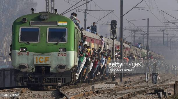 TOPSHOT Indian passengers hang onto a train as it departs from a station on the outskirts of New Delhi on February 28 2017 India's economic growth...