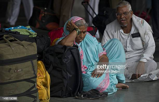 Indian passengers rest on the platform as they wait for their train at a railway station following an overnight regionwide power outtage in New Delhi...