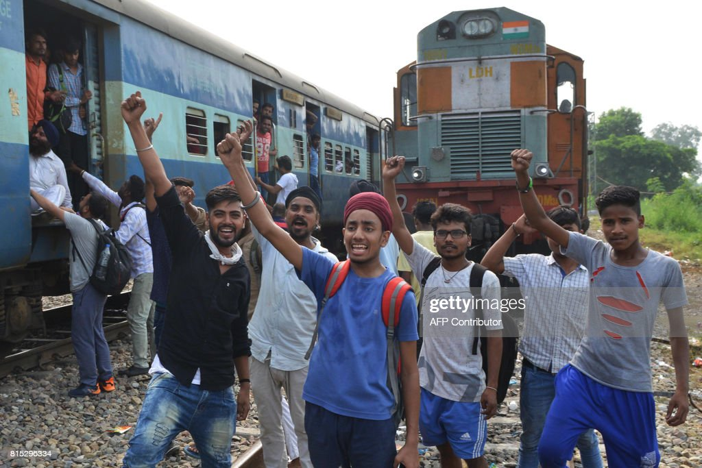 Indian passengers shout slogans during a protest against the railway administration for the regular delays of trains in Manawala railway station...