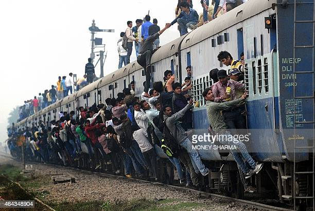 Indian passengers stand and hang onto a train as it departs from a station on the outskirts of New Delhi on February 25 2015 Indian Railways Minister...