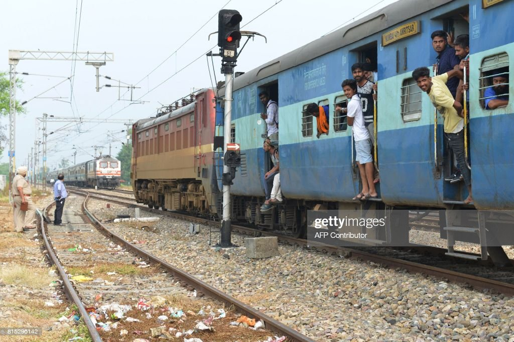 Indian passengers stand at the door of a train carriage after a protest against the railway administration for the regular delays of trains in...