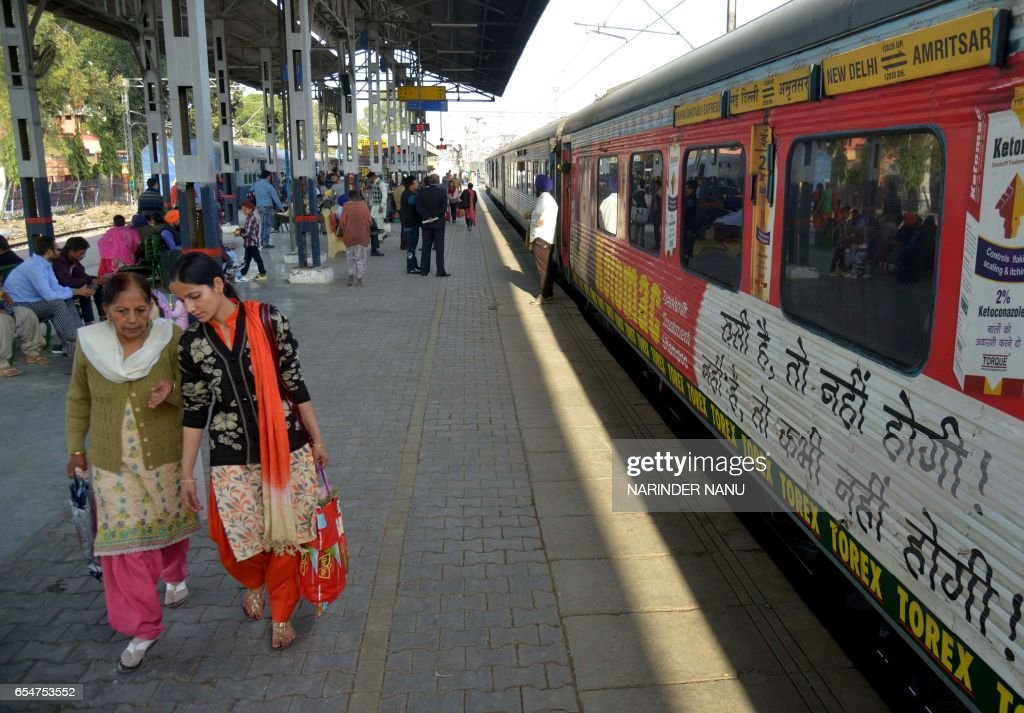 Indian passengers wait for a train as they walk on a platform alongside carriages of The Swarn Shatabdi Express at the railway station in Amritsar on.