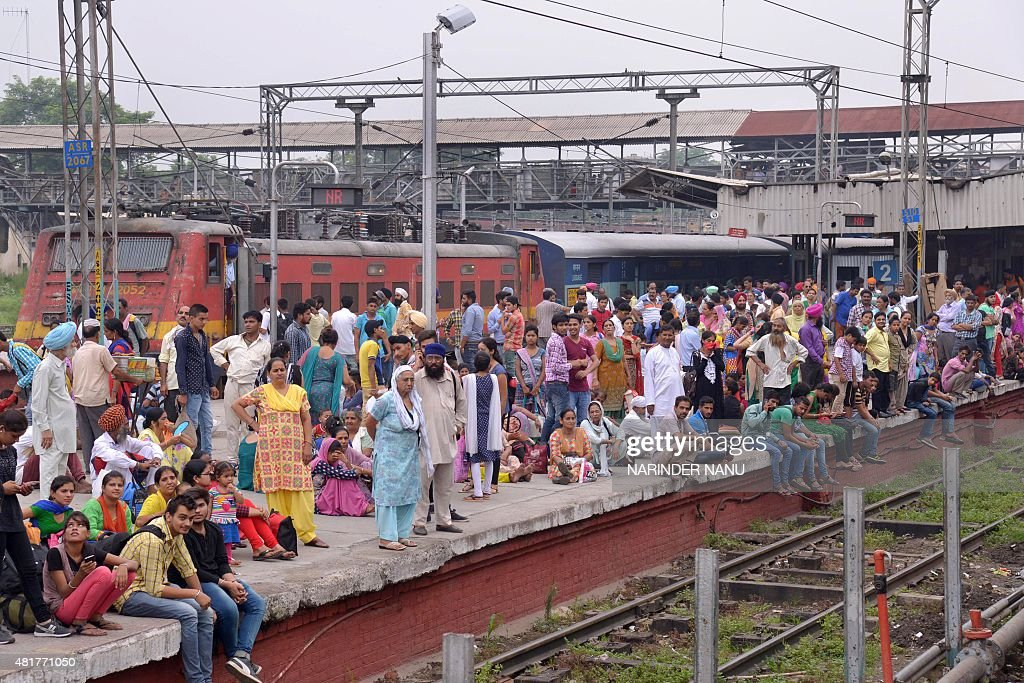 Indian passengers wait for the train at the railway station in Amritsar on July 24 2015 Passengers are facing inconvenience as trains are delayed due.