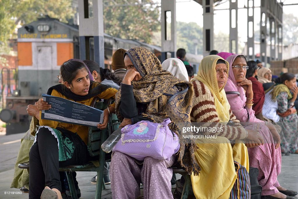 Indian passengers wait for their train at a railway station in Amritsar on February 25 as the annual Railways Budget is announced in parliament in...