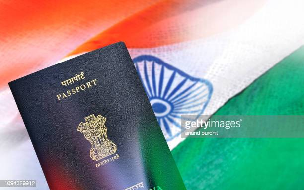 indian passport lying on indian flag - passport stock pictures, royalty-free photos & images