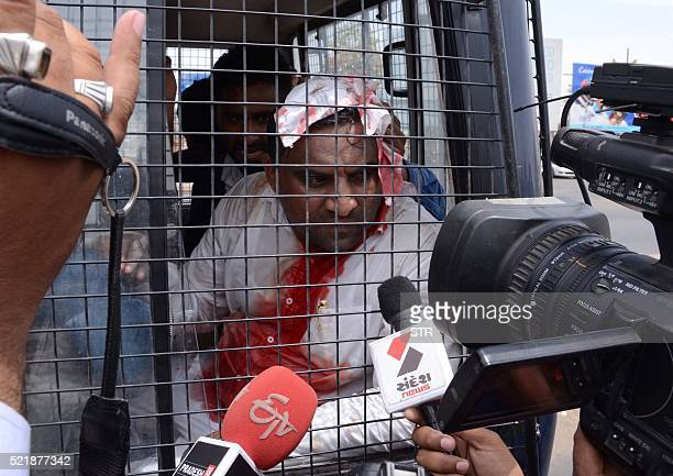 Indian Patel Patidar Community leader Laljibhai Patel sits inside a police van after he was injured in clashes between supporters of Patel Patidar...
