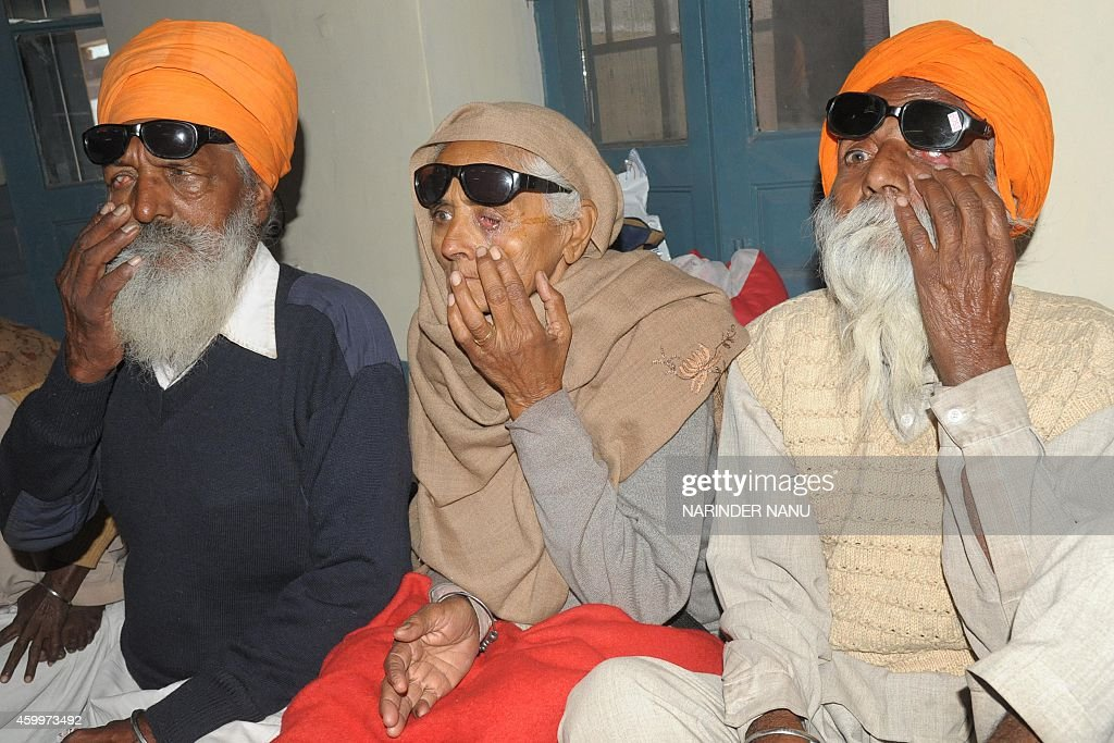 Indian patients Joginder Singh Payar Kaur and Joginder Singh who lost their eyesight after undergoing surgery at an eye camp show their damaged eyes..