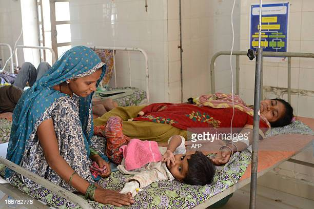 Indian patients suffering from diarrhoea rest in a ward at the Community Health Centre in Dehgam town some 40 kms from Ahmedabad on May 15 2013 Two...