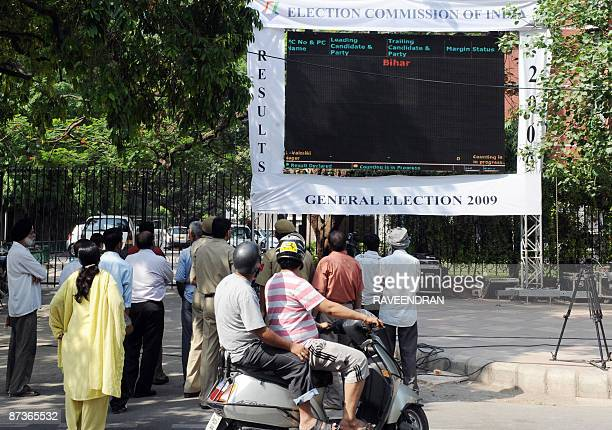 Indian pedestrians and commuters watch a large screen giving details of the country's Parliamentary election results in front of the Election...