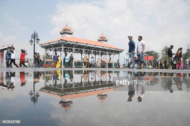 Indian pedestrians are reflected in a puddle after a rainfall in the northern hill town of Shimla on April 7, 2018.