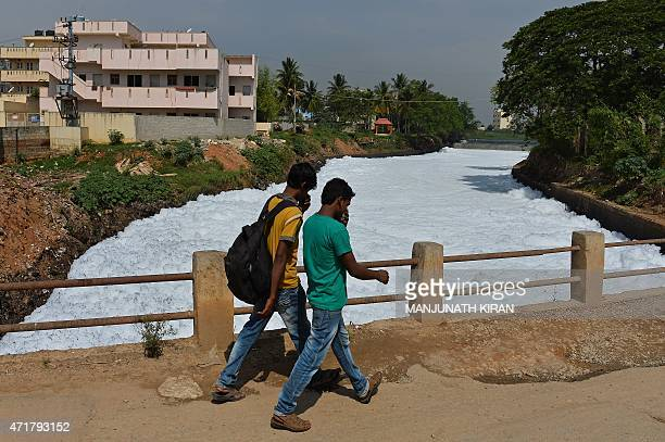 Indian pedestrians cover their noses as they cross a bridge over a frothing canal which once carried water from Bellandur Lake to Varthur Lake in...