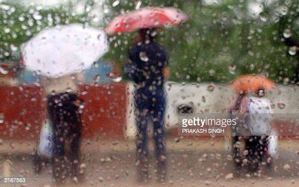Indian pedestrians pictured through a wet car window cross a stree during a monsoon rain shower in New Delhi 18 June 2003 The first premonsoon rain...