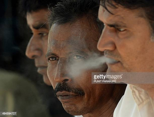Indian pedestrians smoke cigarettes on a street in Mumbai on May 30 2014 The World Health organistan and partners mark World No Tobacco Day on May 31...