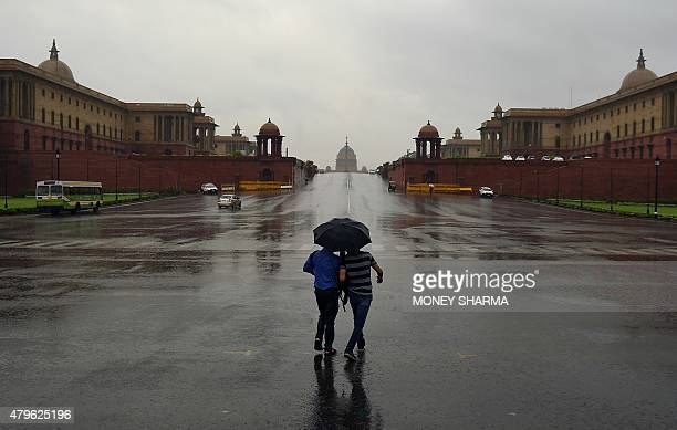 Indian pedestrians use an umbrella to protect themselves from heavy rainfall in New Delhi on July 6 2015 AFP PHOTO/MONEY SHARMA