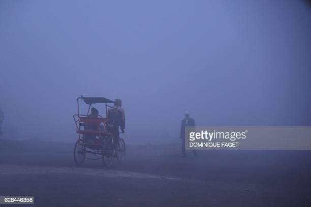 TOPSHOT Indian pedestrians walk along the street on a cold foggy morning in New Delhi on December 8 2016 / AFP / Dominique FAGET