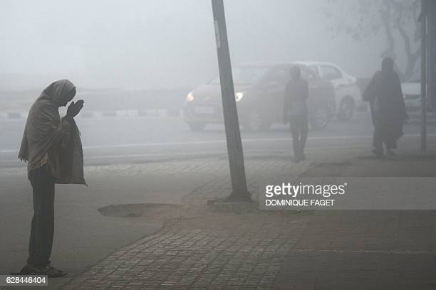 Indian pedestrians walk along the street on a cold foggy morning in New Delhi on December 8 2016 / AFP / Dominique FAGET