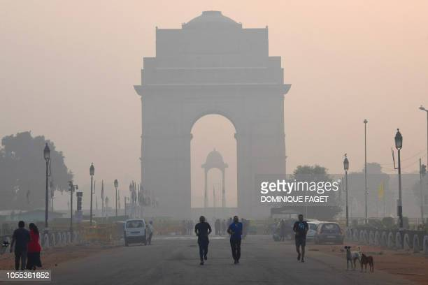 Indian pedestrians walk near the India Gate monument amid heavy smog conditions in New Delhi on October 30 2018 Smog levels spike during winter in...