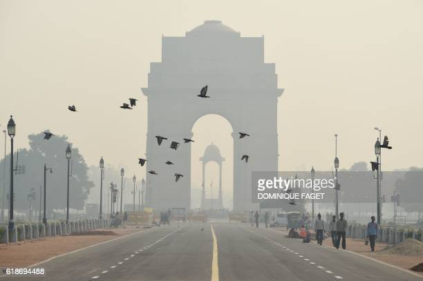 TOPSHOT Indian pedestrians walk near the India Gate monument amid heavy smog in New Delhi on October 28 2016 India's capital with 18 million...