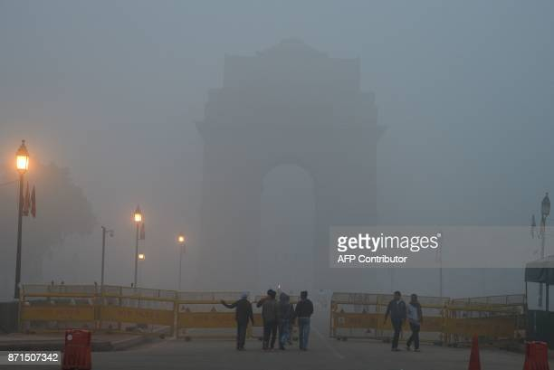 Indian pedestrians walk near the India Gate monument amid heavy smog in New Delhi on November 8 2017 Delhi shut all primary schools on November 8 as...