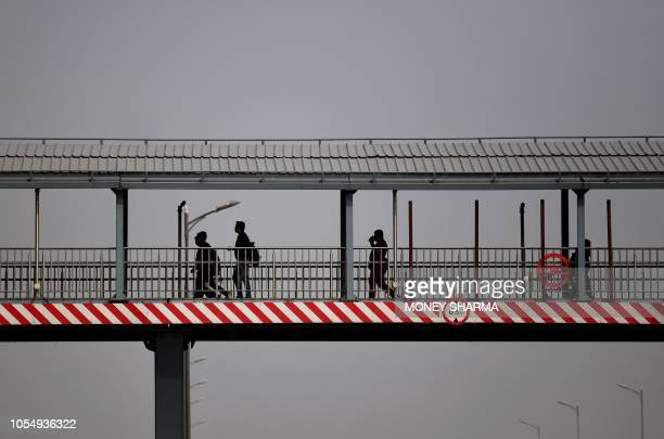 Indian pedestrians walk on a footbridge amid heavy smog conditions in New Delhi on October 29 2018 Smog levels spike during winter in Delhi when air...