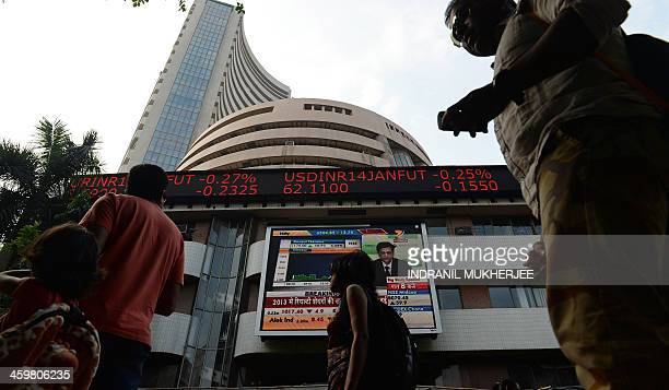 Indian pedestrians walk past the Bombay Stock Exchange building in Mumbai on December 31 2013 Indian shares which remained sluggish for most of 2013...