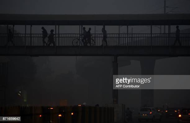 Indian pedestrians walk through heavy smog in Faridabad a suburb of New Delhi on November 8 2017 Delhi shut all primary schools on November 8 as...