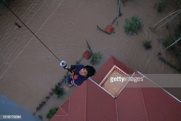 TOPSHOT Indian People are airlifted by Navy personnel during a rescue operation at a flooded area in Paravoor near Kochi in the Indian state of...