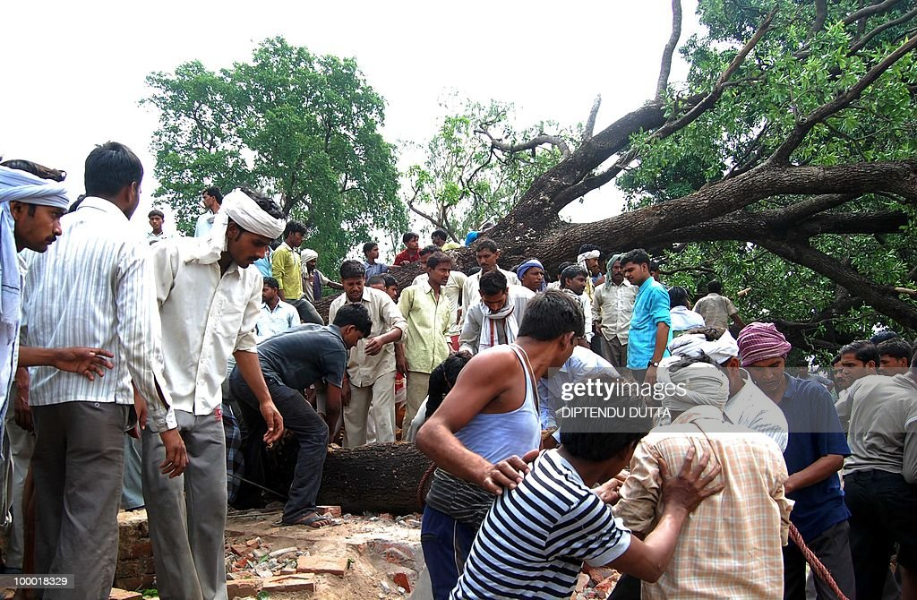 Indian people clear the debris at the site of an uprooted tree and a collapsed buliding after a dust storm in Nababganj village, some 24 kms from Allahabad in Uttar Pradesh, on May 20, 2010. At least nine persons, including two women and a young girl, were killed in the dust storm that hit the district's trans-Ganga region, the Press Trust of India reported. AFP PHOTO / Diptendu DUTTA