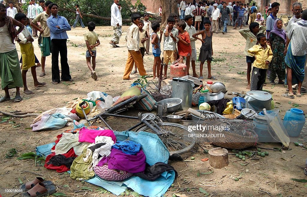 Indian people clear the debris of their belongings at the site of an uprooted tree and a collapsed buliding after a dust storm in Nababganj village, some 24 kms from Allahabad in Uttar Pradesh, on May 20, 2010. At least nine persons, including two women and a young girl, were killed in the dust storm that hit the district's trans-Ganga region, the Press Trust of India reported. AFP PHOTO / Diptendu DUTTA