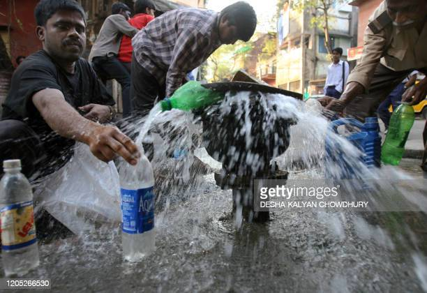 Indian people collect drinking water from a leaking pipeline in Kolkata 22 March 2007 the World Water Day Millions of people in India do not access...