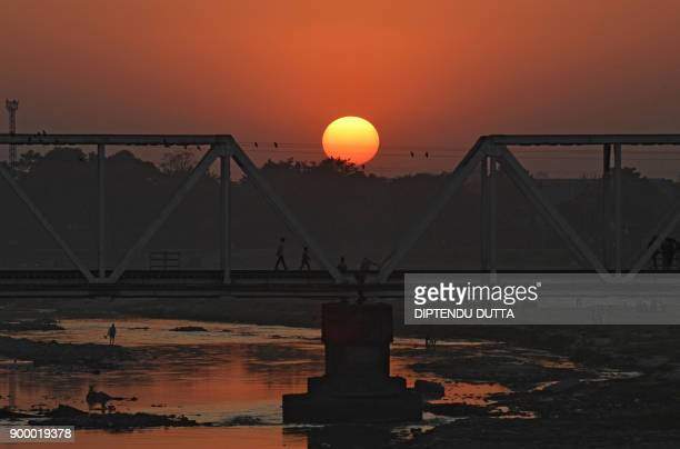Indian people cross a railway bridge as the sun sets on the horizon for the last time this year in Siliguri on December 31 2017 / AFP PHOTO /...