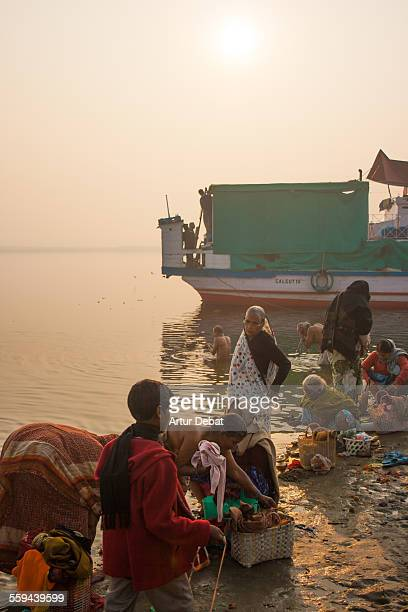 Indian people doing the laundry cleaning clothes on the Ganges river shore in the Varanasi city India Asia