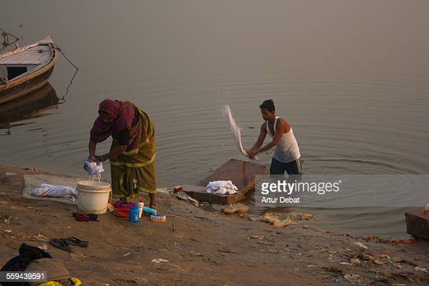 Indian people doing the laundry washing clothes on the Ganges river shore in the Varanasi city India Asia