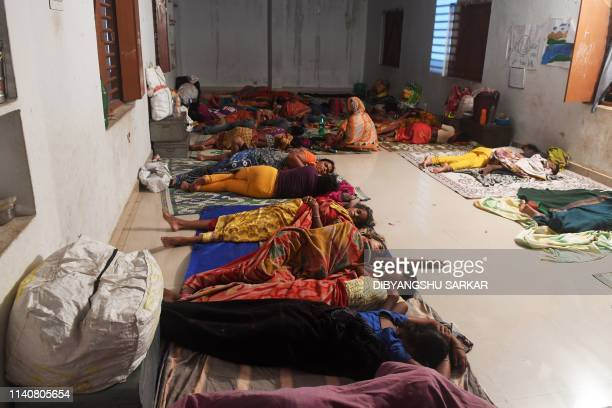 Indian people evacuated for safety rest in a temporary cyclone relief shelter in Puri in the eastern Indian state of Odisha on May 3 as cyclone Fani...