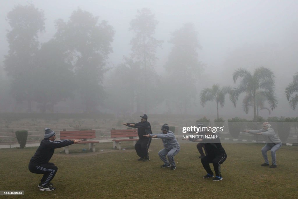 Indian people exercise amid heavy fog and air pollution in Amritsar on January 2 2018 / AFP PHOTO / NARINDER NANU